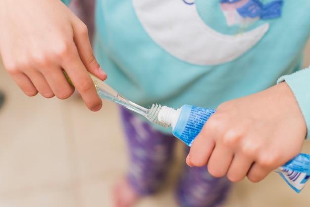 Obenliegende ansicht des mädchens zahnpasta auf zahnbürste setzend Kostenlose Fotos