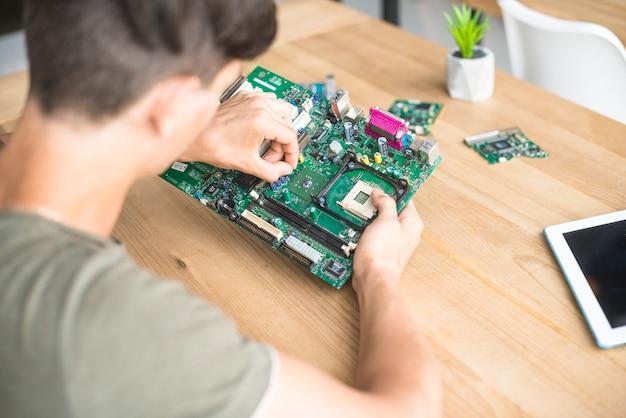 Obenliegende ansicht des mannes computer-hardware-ausrüstung reparierend Kostenlose Fotos