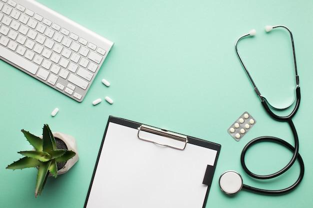 Obenliegende ansicht des medizinischen schreibtisches mit saftiger anlage und drahtloser tastatur auf grüner oberfläche Kostenlose Fotos