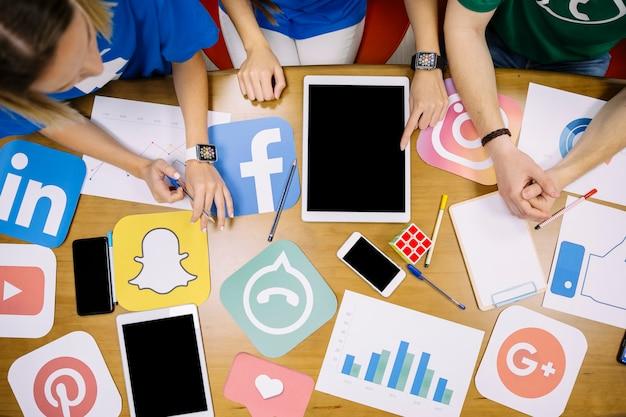 Obenliegende ansicht des teams, das an social media-anwendungen arbeitet Kostenlose Fotos
