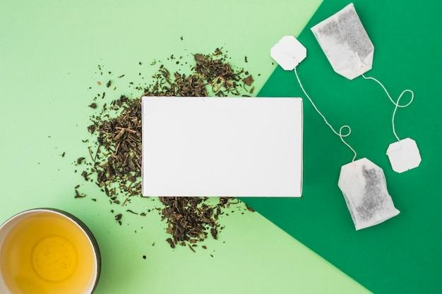 Obenliegende ansicht des weißen kastens mit teeschalen- und teebeuteln auf grünem hintergrund Kostenlose Fotos