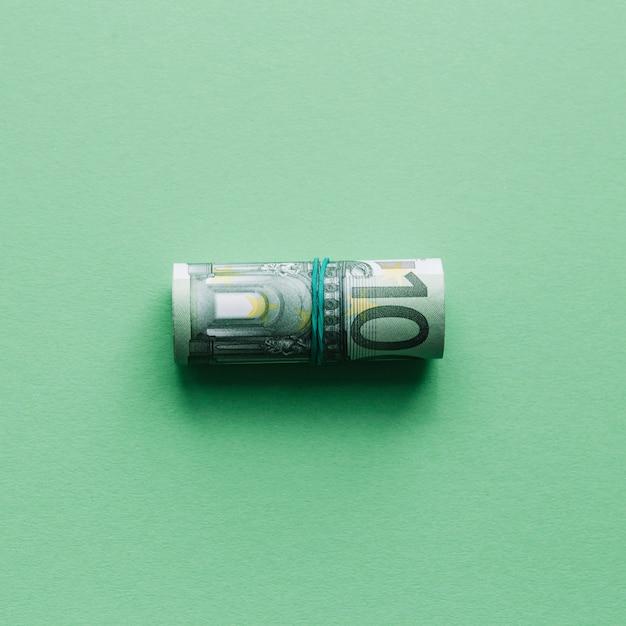 Obenliegende ansicht von aufgerollt herauf hundert euroanmerkung über grüne oberfläche Premium Fotos