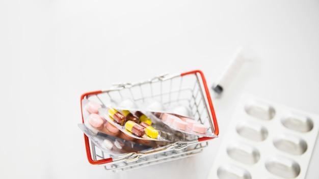 Obenliegende ansicht von blasenpillen im einkaufswagen auf weißem hintergrund Kostenlose Fotos