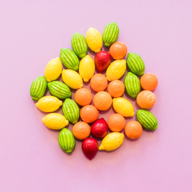 Obenliegende ansicht von bunten fruchtformsüßigkeiten auf rosa hintergrund Kostenlose Fotos