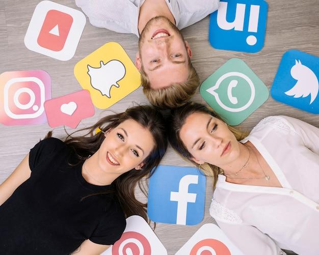 Obenliegende ansicht von den freunden, die auf hintergrund mit social media-ikonen liegen Kostenlose Fotos