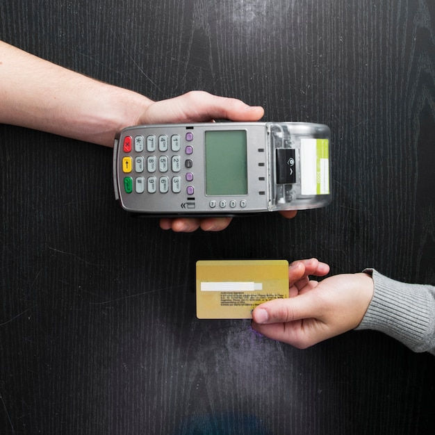 Obenliegende ansicht von den händen, die kartenleser und kreditkarte auf holztisch halten Kostenlose Fotos