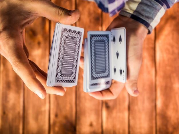 Obenliegende ansicht von den händen, die spielkarten auf der holzoberfläche mischen Premium Fotos