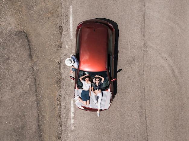 Obenliegende ansicht von freunden mit auto auf straße Kostenlose Fotos