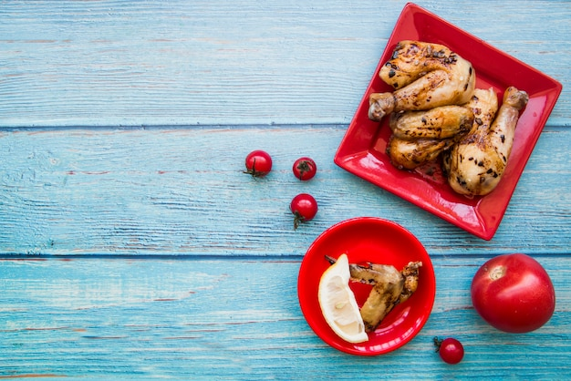 Obenliegende ansicht von gebratenen hühnerbeinen und von hühnerflügeln in der roten platte mit tomaten und zitronenscheibe gegen blauen hölzernen schreibtisch Kostenlose Fotos