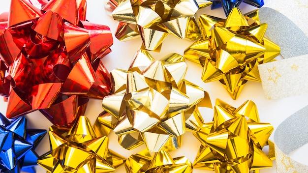 Obenliegende ansicht von goldenem; rote und blaue dekorative bänder auf weißem hintergrund Kostenlose Fotos