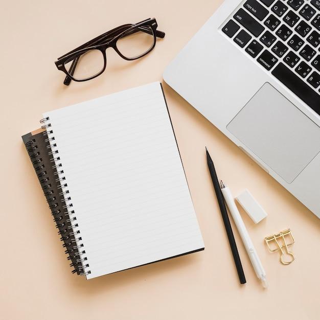 Obenliegende ansicht von schreibwaren und von laptop auf beige hintergrund Kostenlose Fotos