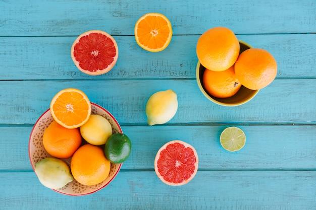 Obenliegende ansicht von verschiedenen zitrusfrüchten auf blauem hölzernem hintergrund Kostenlose Fotos