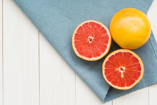 Obenliegende ansicht von zitrusfrüchten und von stoff auf hölzernem hintergrund Kostenlose Fotos