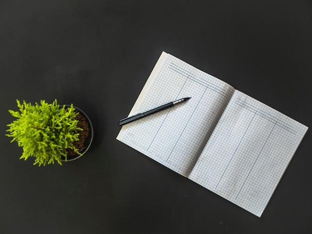 Obenliegender geöffneter leerer wortschatz mit stift auf schwarzer tabelle mit blume Premium Fotos
