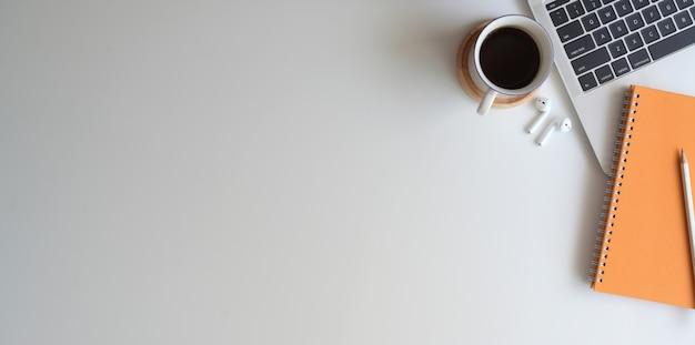 Obenliegender schuss des bequemen arbeitsplatzes mit notizbuch auf weißem schreibtischhintergrund Premium Fotos