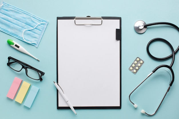 Obenliegendes ansichtgesundheitswesenzubehör nahe klemmbrett mit plankenpapier und schauspielen auf hintergrund Kostenlose Fotos