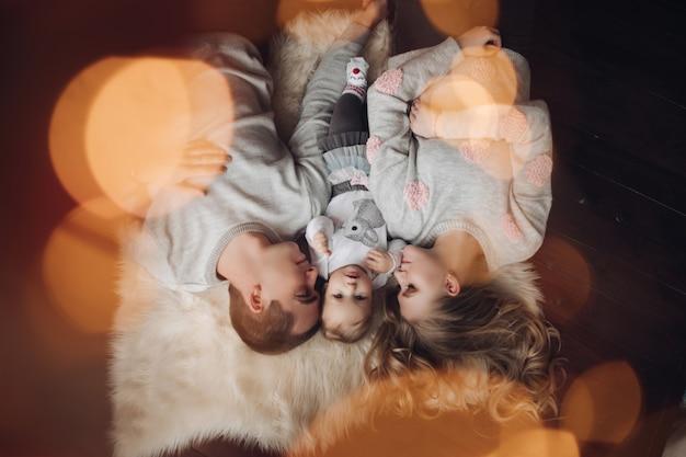 Obenliegendes porträt der schönen familie auf pelzteppich Premium Fotos