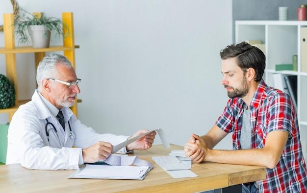 Oberarzt, der mit patienten spricht Kostenlose Fotos