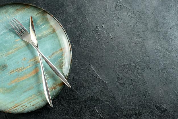 Obere hälfte ansicht gekreuztes messer und gabel auf runder platte auf schwarzem tischkopierplatz Kostenlose Fotos