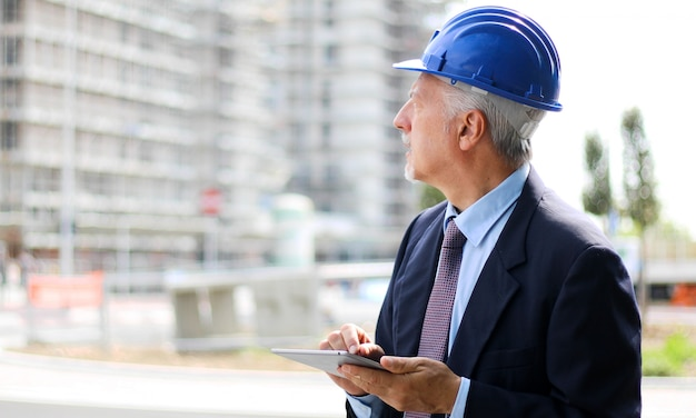 Oberingenieur mann in anzug und helm arbeiten an tabletpc Premium Fotos
