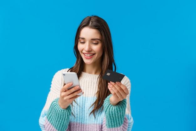 Oberkörperaufnahme entspannte sich und lächelte herrliche frau in der winterstrickjacke und zahlte für kauf, schickte dem freund mit app geld, fügte rechnungsinformationen, kreditkartennummer an der anwendung ein und hielt smartphone Premium Fotos