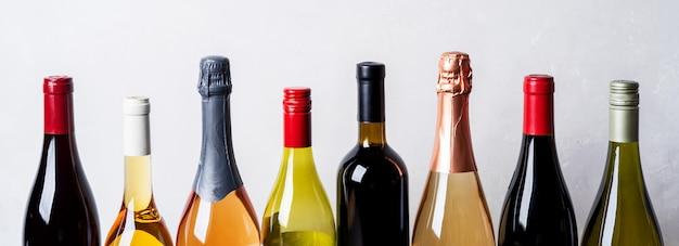 Oberteile von neuen flaschen champagner, weißwein, rotwein auf hellem hintergrund Premium Fotos