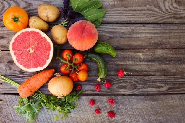 Obst, gemüse diät auf hölzernen hintergrund Premium Fotos