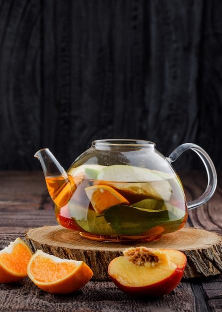 Obst infundierte wasser mit früchten, holz in der teekanne auf steinfliesen und holzoberfläche Kostenlose Fotos