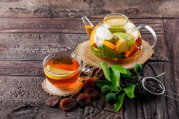 Obst infundiertes wasser in der teekanne mit getrockneten aprikosen, holz, behälter, limetten-hochwinkelansicht auf einer steinfliesenoberfläche Kostenlose Fotos