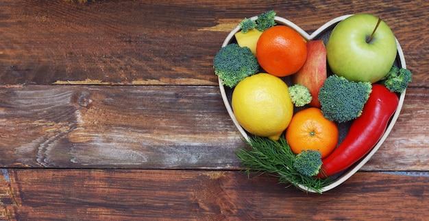 Obst und gemüse in herzförmiger holzkiste. brokkoli, äpfel, pfeffer, mandarine über holztisch. biokost-konzept mit copyspace. Premium Fotos