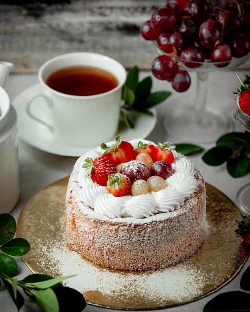 Obstkuchen mit erdbeerweißen und roten trauben gekrönt Kostenlose Fotos
