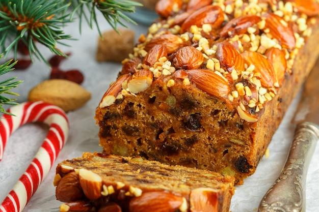 Obstkuchen. traditioneller weihnachtskuchen mit mandeln, getrockneten moosbeeren, zimt, kardamom, anis, nelken Premium Fotos