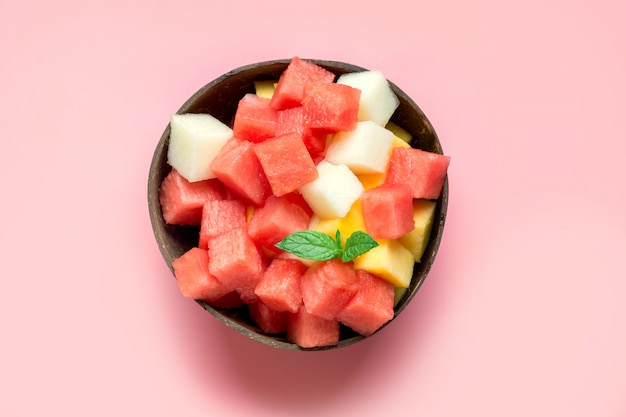 Obstsalat der wassermelone, der melone und der mango in der kokosnussschüssel auf rosa hintergrund. Premium Fotos