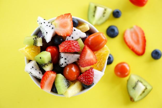 Obstsalat schüssel frischen sommer obst und gemüse gesunde bio-lebensmittel erdbeeren orange kiwi heidelbeeren drachenfrucht tropische trauben ananas tomaten zitrone auf gelb Premium Fotos