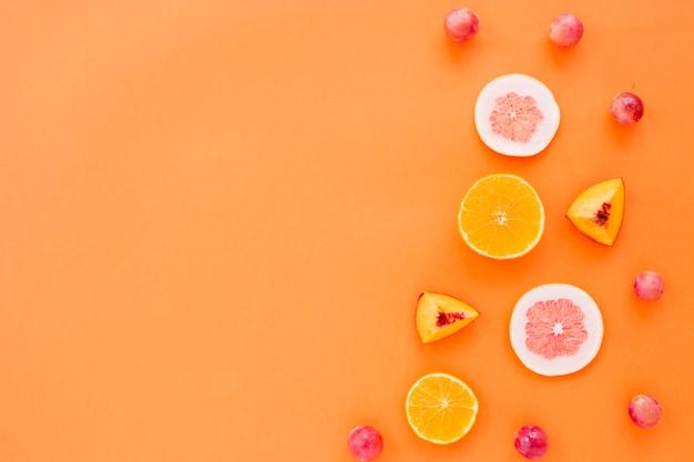 Obstscheiben von orange; grapefruit und pfirsich mit trauben auf einem orangefarbenen hintergrund Kostenlose Fotos
