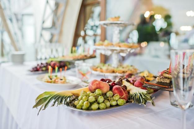 Obstteller mit ananas, trauben und pfirsich im restaurant Premium Fotos