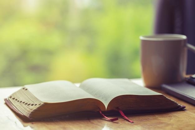 Öffnen sie bibel mit einem tasse kaffee für morgenandacht auf holztisch mit fensterlicht Premium Fotos