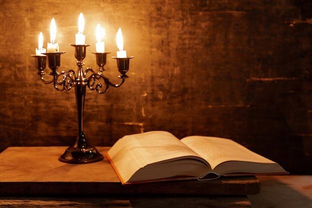 Öffnen sie bibel und kerze auf einem alten eichenholztisch. schöner goldener hintergrund. religion-konzept. Kostenlose Fotos