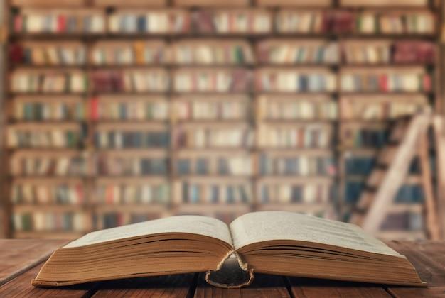 Öffnen sie das buch auf dem tisch in der bibliothek Premium Fotos