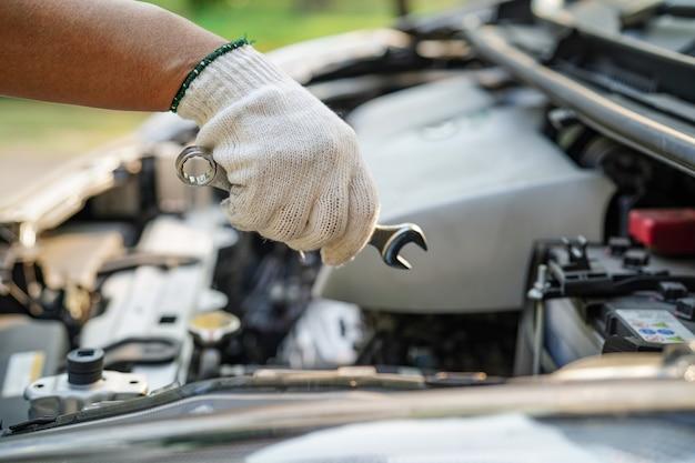 Öffnen sie das motorsystem des motorhaubenmechanikers, um einen beschädigten autounfall zu überprüfen und zu reparieren Premium Fotos