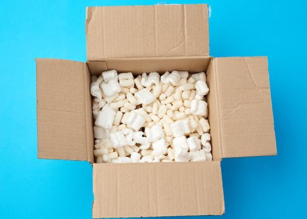 Öffnen sie den braunen karton mit weißer schaumfüllung für den warentransport Premium Fotos