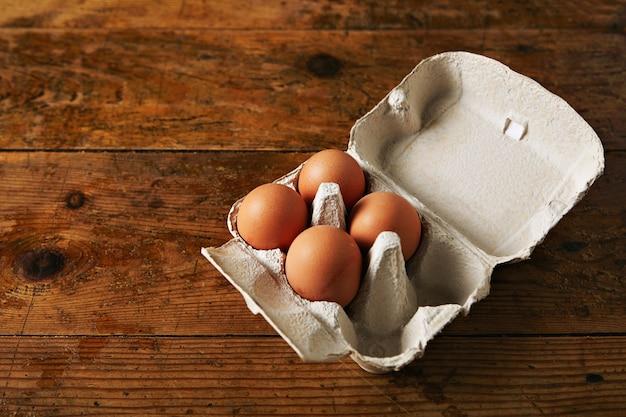 Öffnen sie den eierkarton für sechs eier mit vier braunen eiern auf einem rauen, rustikalen, braunen holztisch Kostenlose Fotos