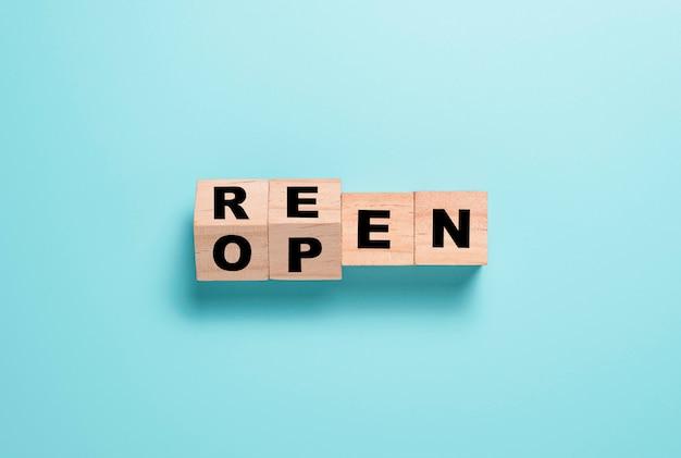 Öffnen sie den trennbildschirm der formulierung auf dem holzwürfelblock erneut. einkaufszentrum und restaurants öffnen nach covid 19 wieder. Premium Fotos
