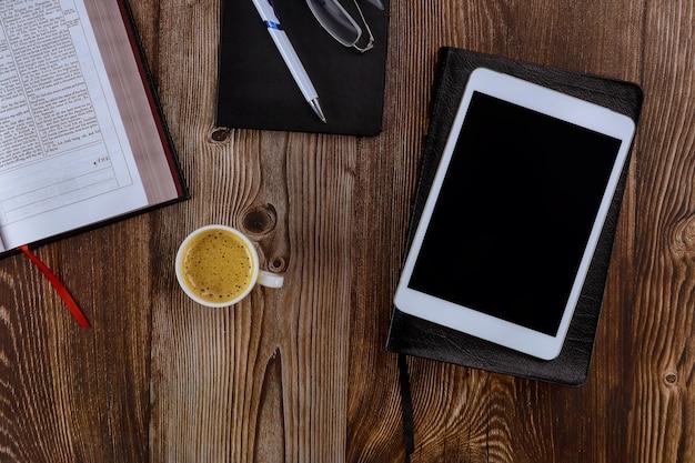 Öffnen sie die heilige bibel, die auf einem holztisch in einer lesung der digitalen tafel mit einer tasse kaffee liegt Premium Fotos