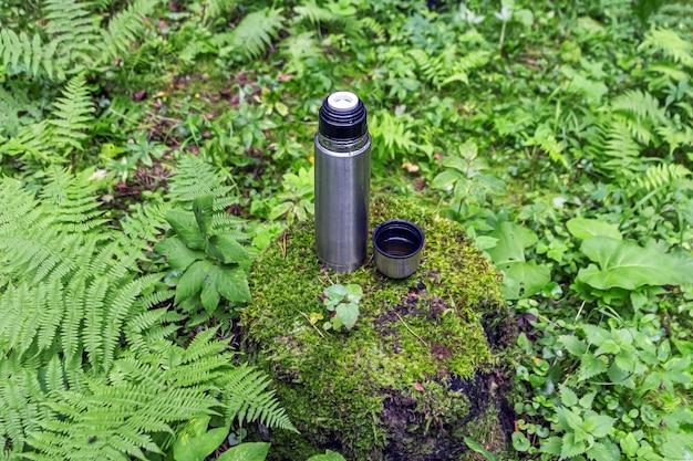 Öffnen sie die thermoskanne aus rostfreiem stahl mit einem teegetränk auf einem baumstumpf im nadelwald Premium Fotos