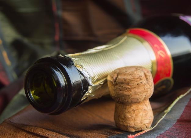 Öffnen sie eine flasche champagner und den korken auf dem tisch mit einer tischdecke Premium Fotos