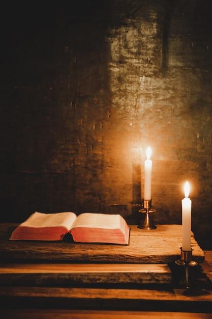 Öffnen sie heilige bibel und kerze auf einem alten eichenholztisch. Kostenlose Fotos