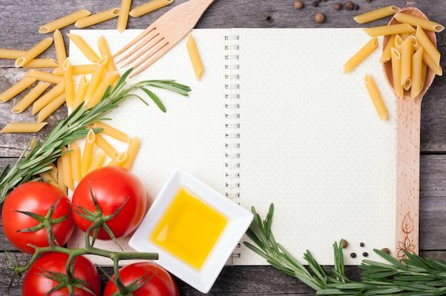 Öffnen sie kochbuch, löffel mit penne pasta, tomaten, rosmarin und olivenöl in einer schüssel auf holzhintergrund Premium Fotos
