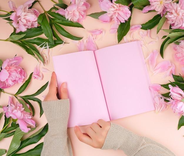 Öffnen sie leeres notizbuch mit rosa blättern und blühenden pfingstrosen mit grünen blättern Premium Fotos