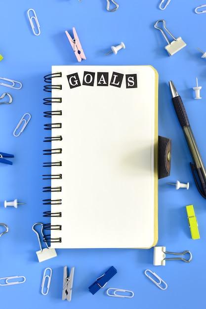 Öffnen sie notizbuch auf blau mit dem wort ziel. Premium Fotos